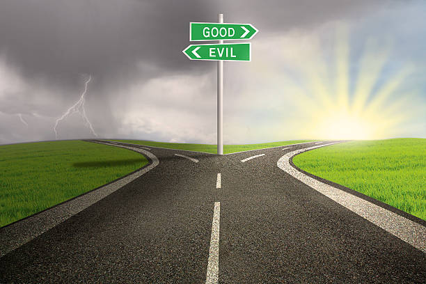 road sign of good vs evil - diabolic stock pictures, royalty-free photos & images