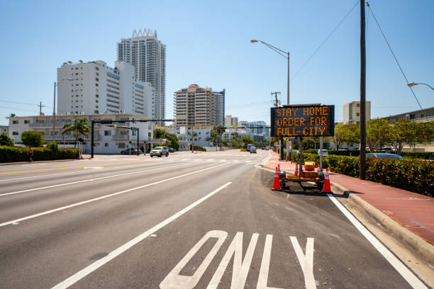 het teken van de weg op het strand van miami dat woorden toont blijf huisorde voor volledige stad om verspreiding van coronavirus te langzaam - avondklok stockfoto's en -beelden