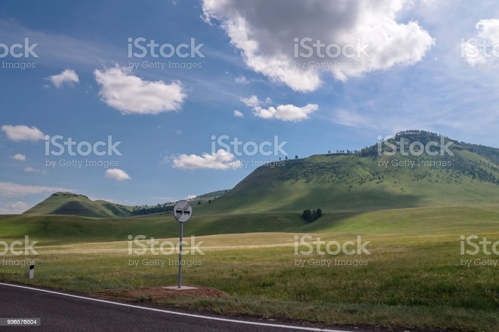 A road sign on the roadside, against the backdrop of blossoming Khakass mountains. stock photo