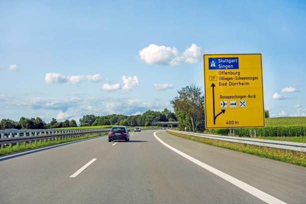 road sign on through road with car road sign on through road (Bundesstrasse B 27) showing way to german autobahn directions Stuttgart / Singen singen stock pictures, royalty-free photos & images