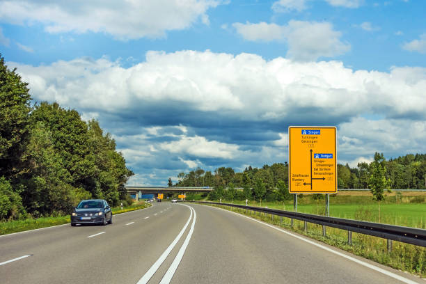 road sign on through road with car road sign on through road (Bundesstrasse B 31) showing way to german autobahn direction Singen and Stuttgart singen stock pictures, royalty-free photos & images