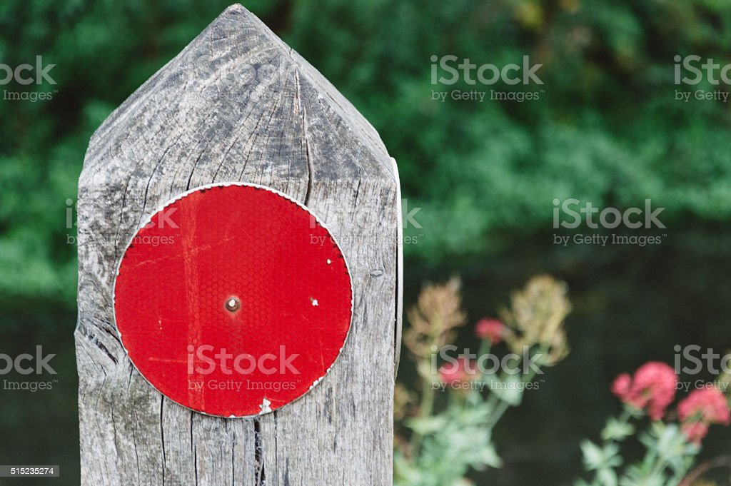 Road sign with a red point on a wood stake stock photo