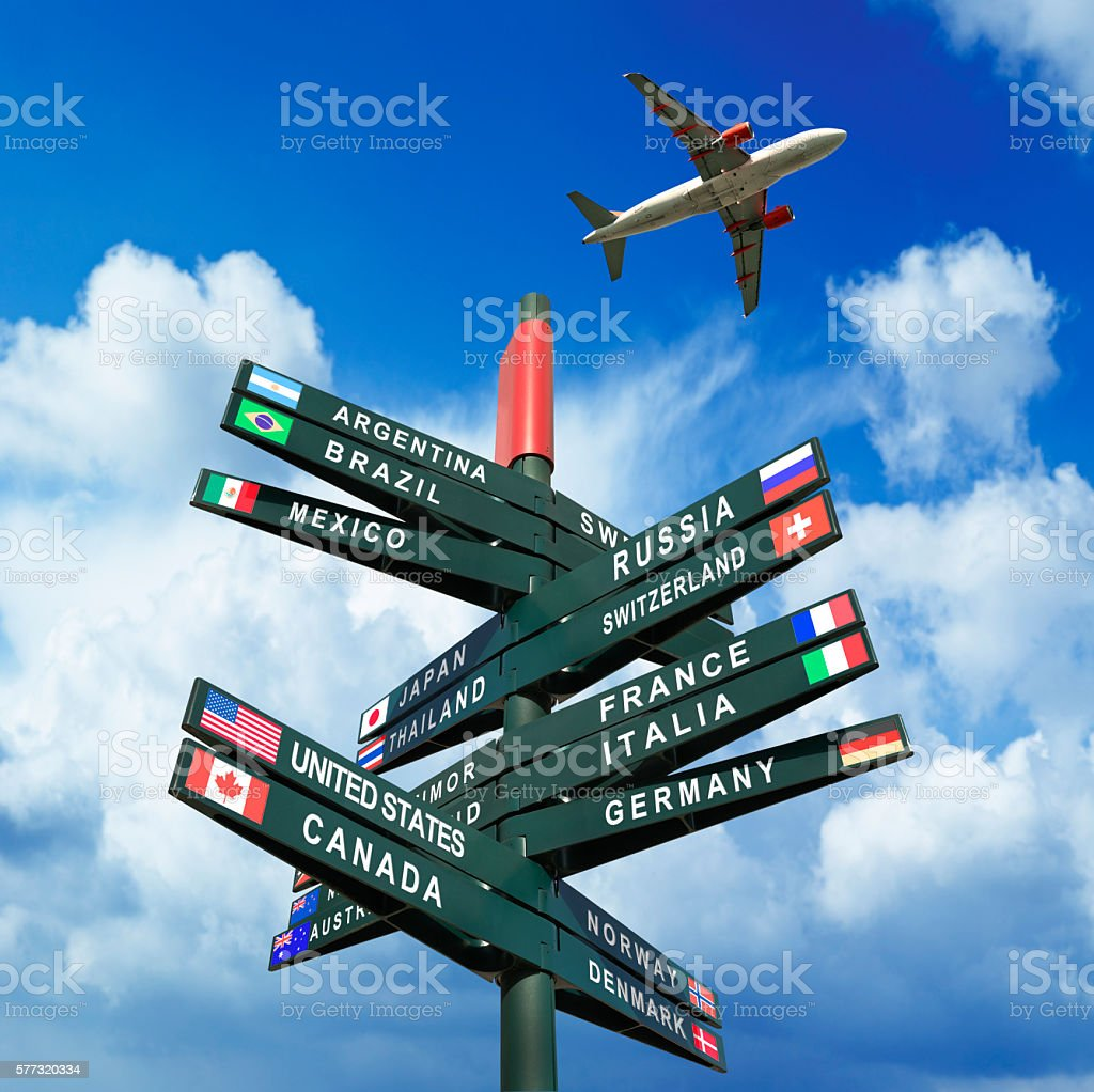 Road sign with flags from countries, plane in the sky stock photo