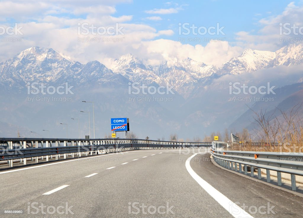 Road sign with indication to go lake Como in Italy. Traffic on hihgway in the Italian Alps stock photo