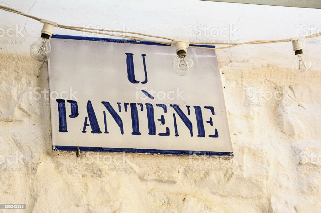 Road sign with street dialect name in a Puglia road stock photo