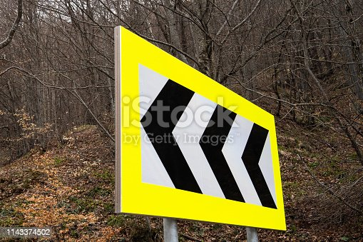 istock Road Sign Yellow White Black Arrows left turn danger curves 1143374502