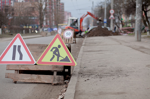 istock Road signs, detour, road repair on street background, truck and excavator digging hole 1142628087