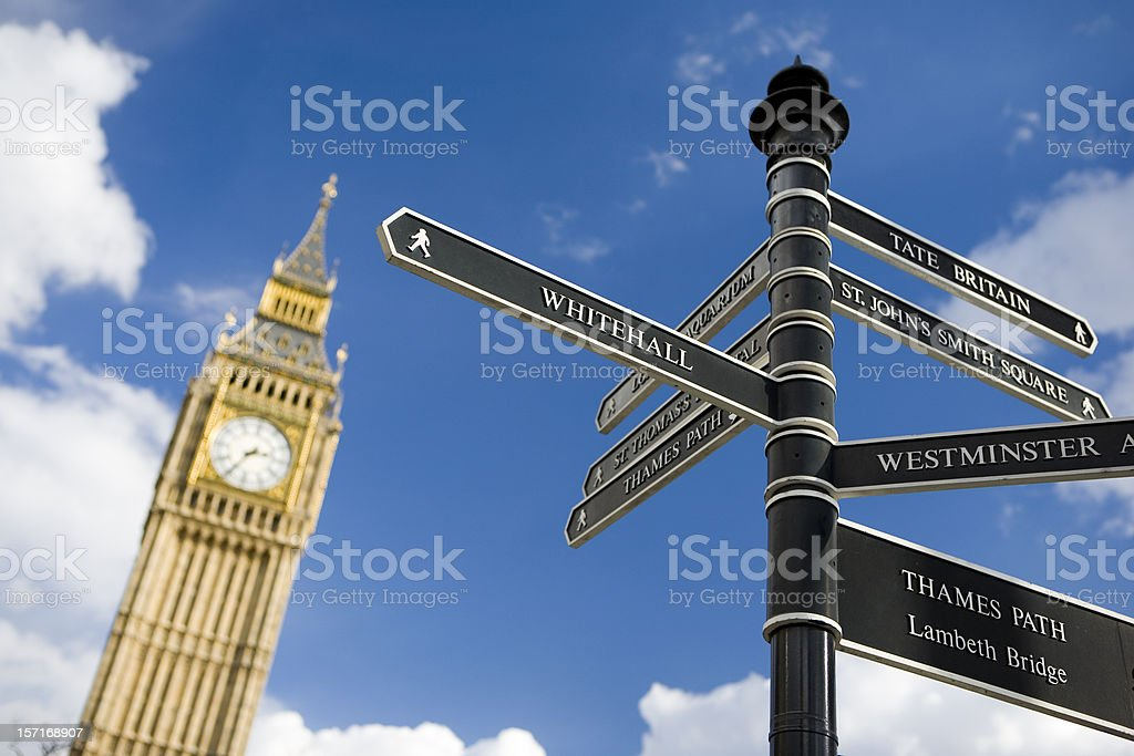 Road signs in London, with clock tower in background.  stock photo