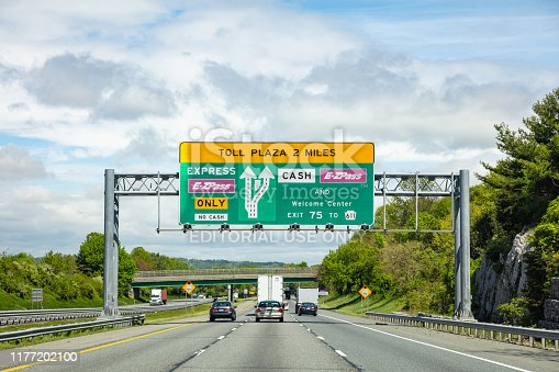 Pennsylvania highway, USA. May 6, 2019: Toll plaza information road signs billboard on the highway, cloudy sky