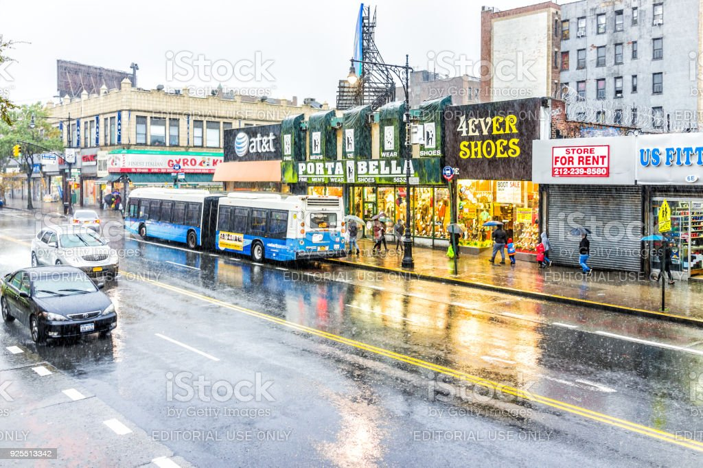 Road street in Fordham Heights center with cars traffic, New York City, NYC during heavy rain, people umbrellas, stores shops stock photo