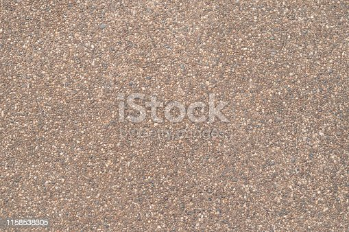 Road surface of small pebbles brown, top view.