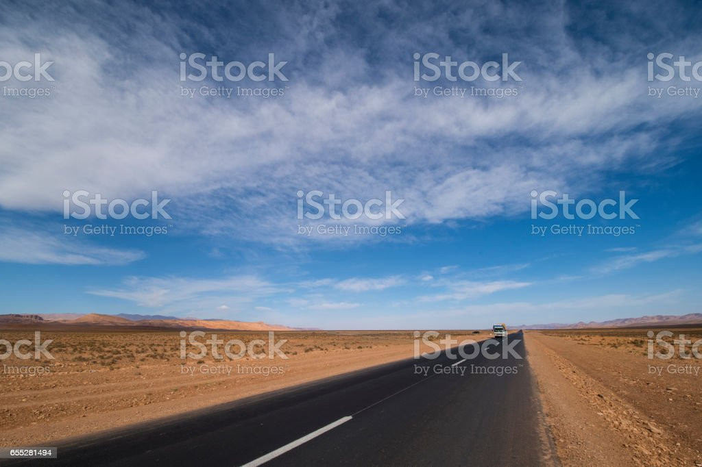 Road though the desert and sand dunes of Morocco and Sahara with blue sky! stock photo