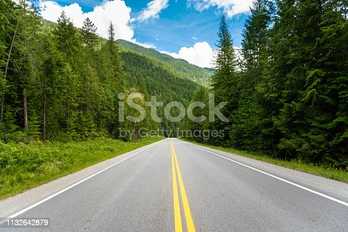 Empty Straight Stretch of a Mountain Road through a Beautiful Dense Forest in British Columbia, Canada, on a Clear Summer Day
