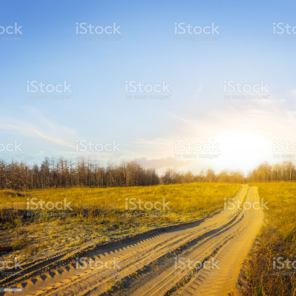 road through a sandy desert at the sunset stock photo