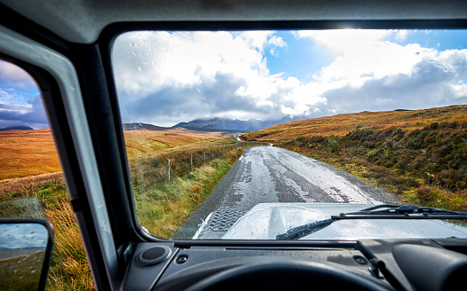 A road through a Scottish landscape seen though a window of a 4x4 near the Fairy Pools
