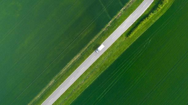 Straße durch landwirtschaftliche Fläche-Luftaufnahme – Foto
