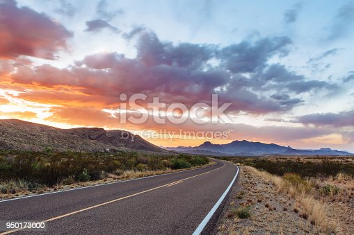 istock Road through dramatic sunset and sky over desert landscape 950173000