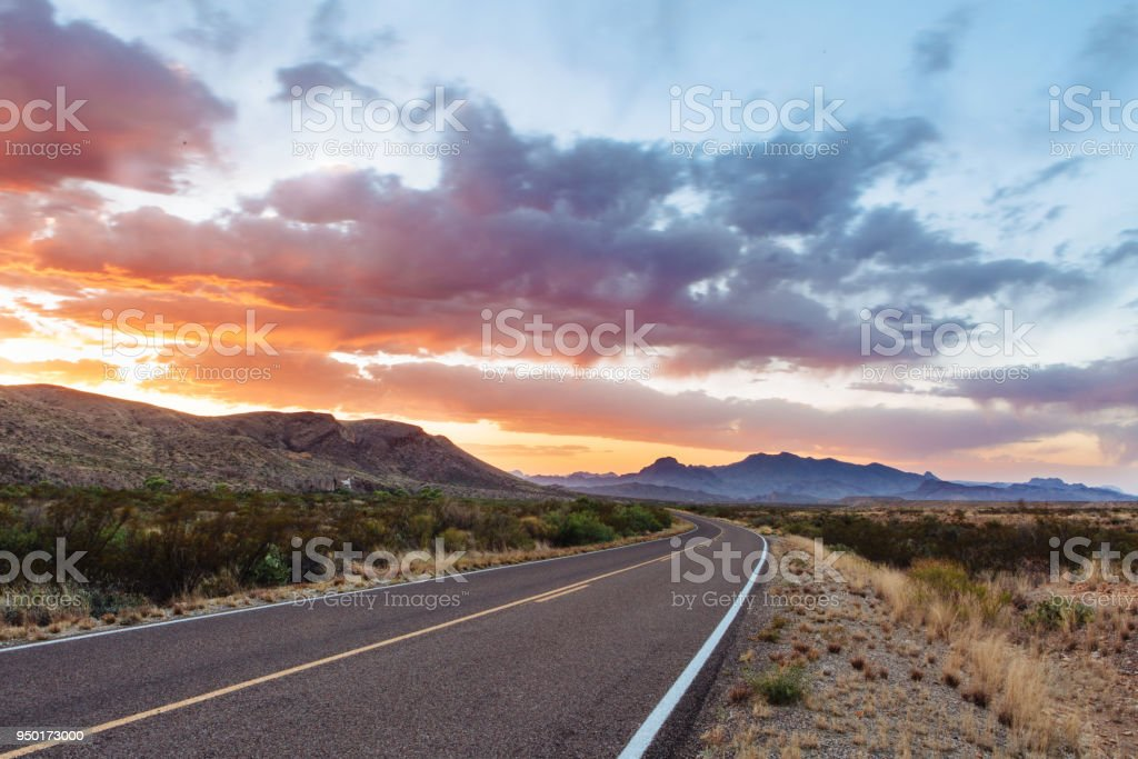 Road through dramatic sunset and sky over desert landscape stock photo