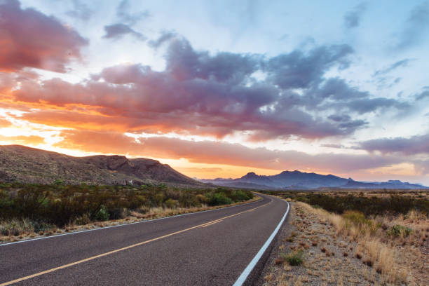 road through dramatic sunset and sky over desert landscape - estrada imagens e fotografias de stock