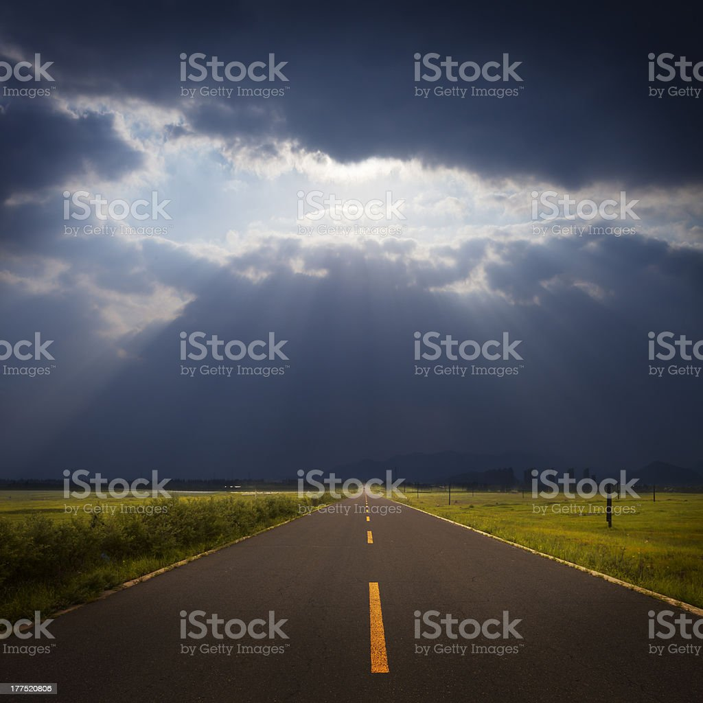 road through grassland with cloud and ray light royalty-free stock photo