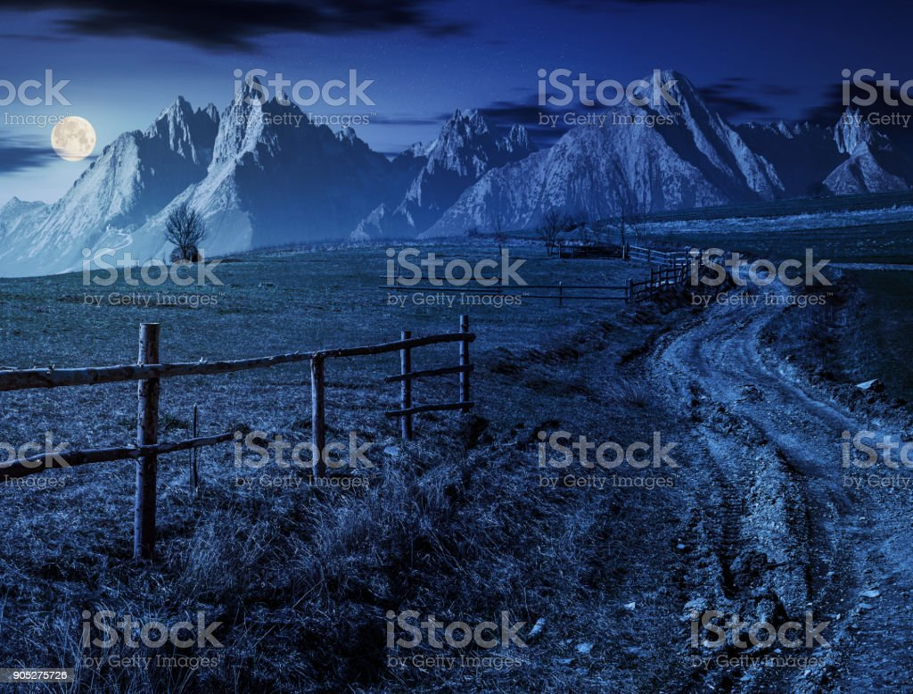 road through rural fields in mountains at night stock photo