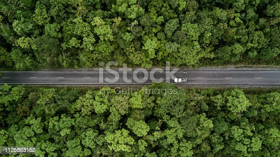 istock Road through the green forest, aerial view road going through forest. 1125863152