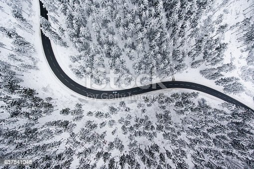 istock Road through the wintery forest - aerial view 637841048