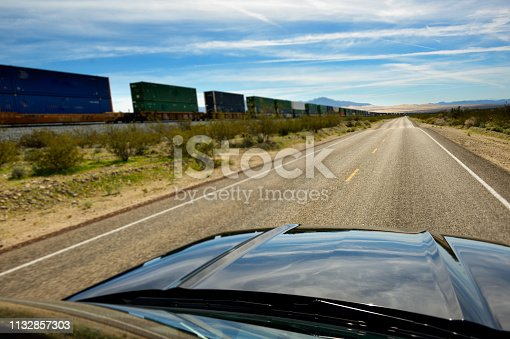 Car driving on deserted, straight freeway portion, parallel to railroad with long cargo train.
