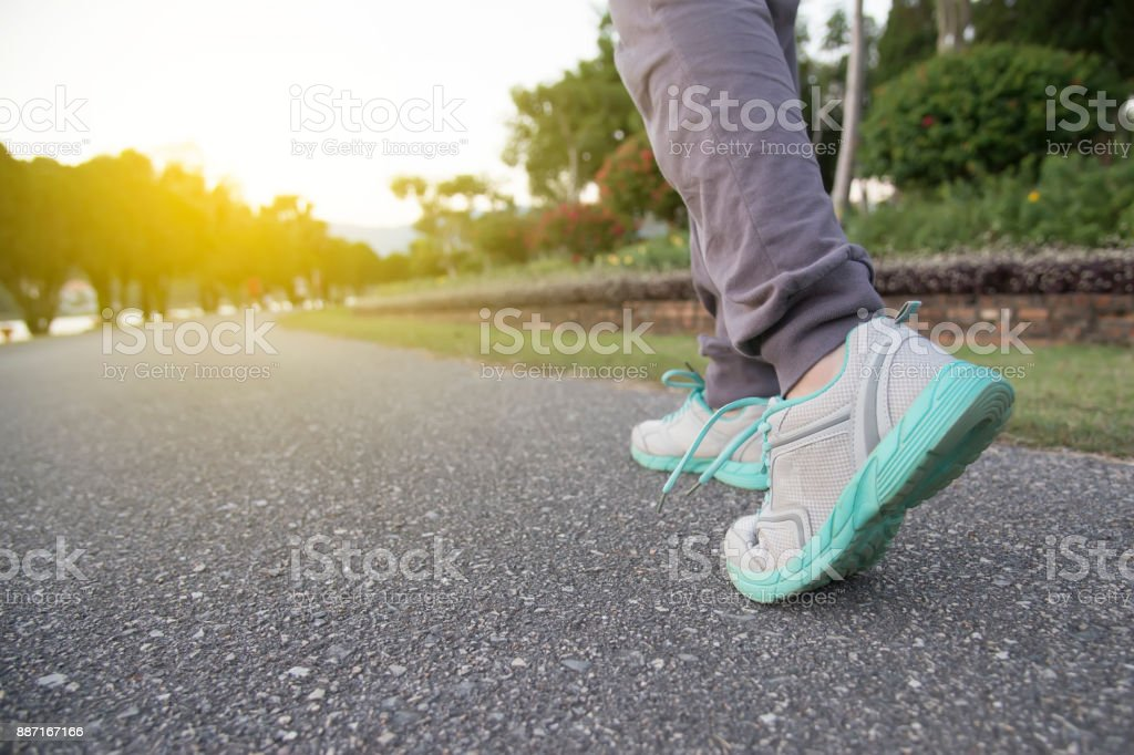 Road to success,running on road with sports shoes,healthy lifestyle sports woman running, female legs with sneakers jogging in evening prepare for marathon stock photo