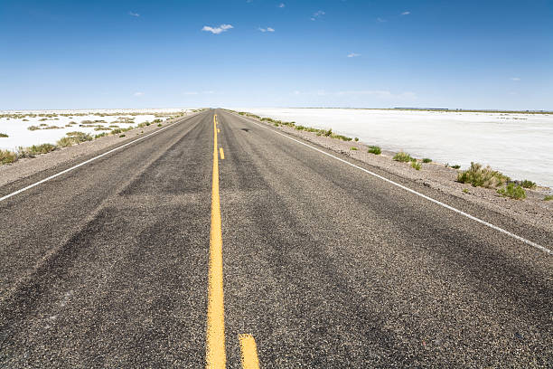 Road to the horizon On the road to the Bonneville Speedway, Bonneville Salt Flats near Wendover, Utah, United States bonneville salt flats stock pictures, royalty-free photos & images