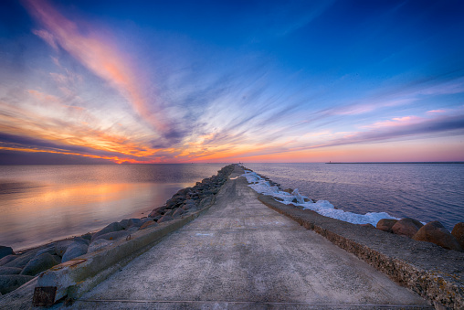 Road to the lighthouse. Sunset at the Baltic sea