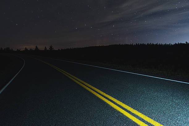 Road to the North A wide view of the Big Dipper and faint Northern Lights over a coastal roadway.  Long exposure. big dipper constellation stock pictures, royalty-free photos & images