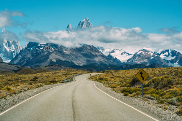 Road to the snowy mountains blue sky and clouds stock photo