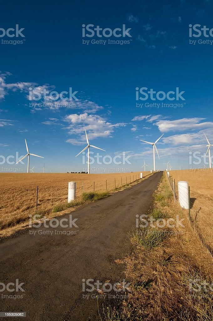 Road to Wind Power A dirty road leading to the Curve Stock Photo