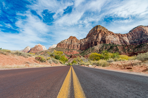 Front view photography from a car driving on an asphalt road with yellow lines through Zion National Park in Utah, USA.