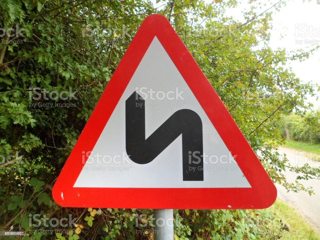 Road traffic hazard warning sign 'Double Bend First To Left' stock photo