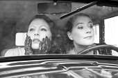 Two women in a vintage car - 1930 style. Black and white image.