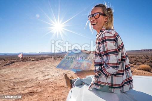 841604240istockphoto USA road trip adventure; woman looking at map 1159351813
