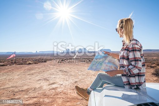 841604240 istock photo USA road trip adventure; woman looking at map 1159352274