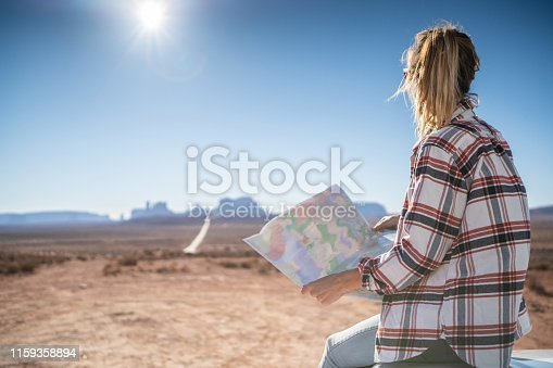 841604240 istock photo USA road trip adventure; woman looking at map 1159358894