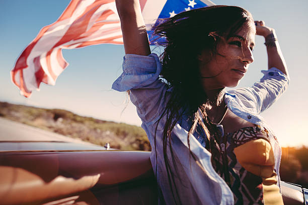 Road Trip boho girl holds American Flag on convertible car stock photo