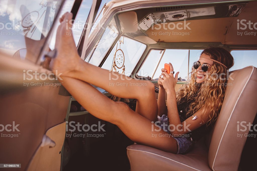 Road Trip Boho Girl Sitting in vintage Van with smartphone stock photo