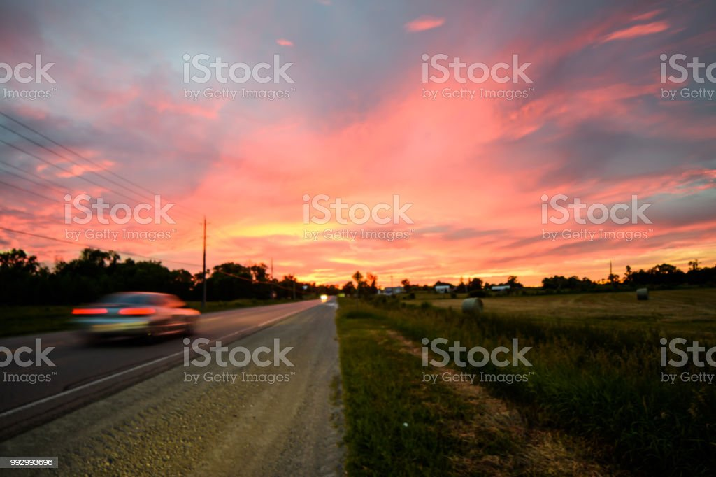 Road trip car on country road moving fast with scenic sunset and pink sky on horizon stock photo