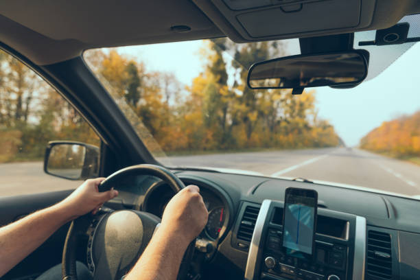 road trip concept man hands on steering wheel navigation on the phone stock photo
