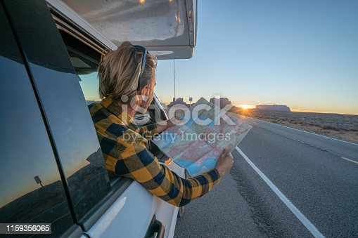 Road trip concept; Young man inside RV looking at road map for directions exploring national parks and nature ready for adventure
