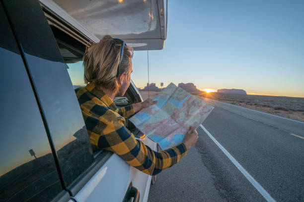 Road trip concept; Young man inside campervam looking at road map for directions exploring national parks and nature ready for adventure. stock photo