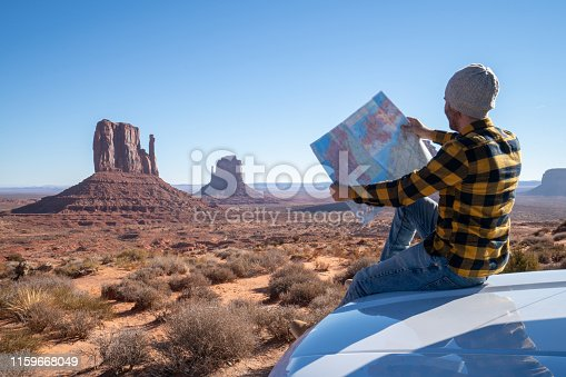 Road trip concept; Young man outside car looking at road map for directions exploring national parks and nature ready for adventure
