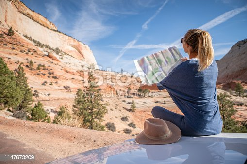 841604240 istock photo Road trip concept; Young woman sitting on car's hood looking at road map for directions exploring national parks and nature ready for adventure. 1147673209