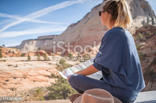 841604240 istock photo Road trip concept; Young woman sitting on car's hood looking at road map for directions exploring national parks and nature ready for adventure. 1147674078