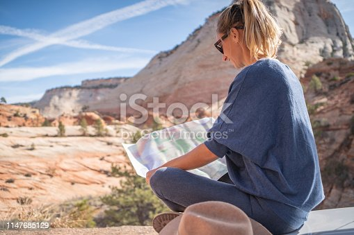 841604240 istock photo Road trip concept; Young woman sitting on car's hood looking at road map for directions exploring national parks and nature ready for adventure. 1147685129